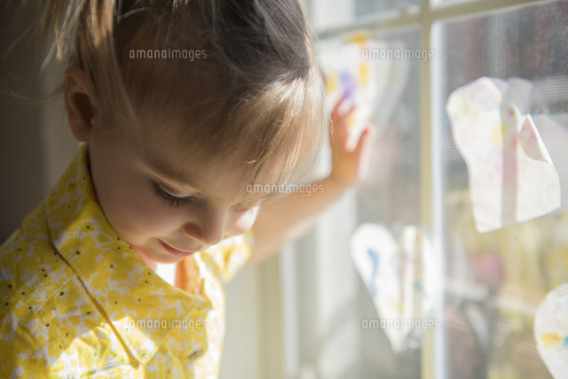 Caucasian baby girl leaning on window