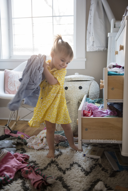 Caucasian baby girl removing clothing from dresser drawer