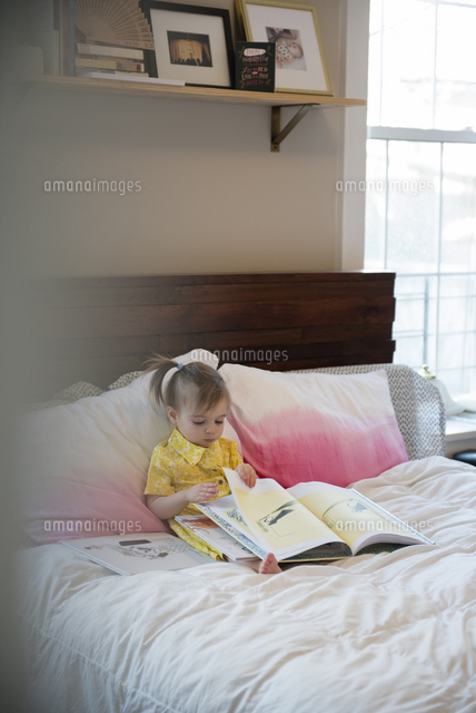 Caucasian baby girl sitting on bed reading book