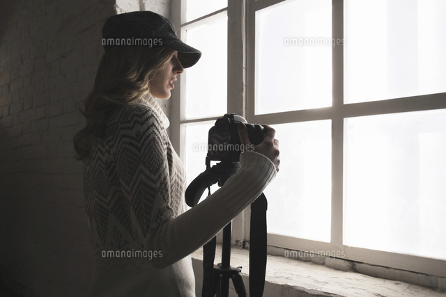 Caucasian woman near window holding camera