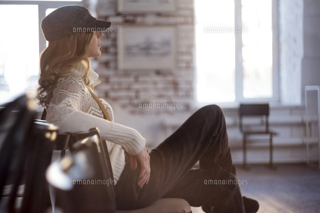 Caucasian woman sitting in chair with legs crossed