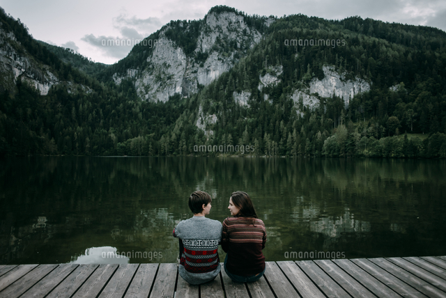 Caucasian couple sitting on dock near scenic view of mountain