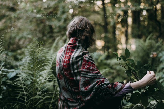 Caucasian woman holding green leaf in forest