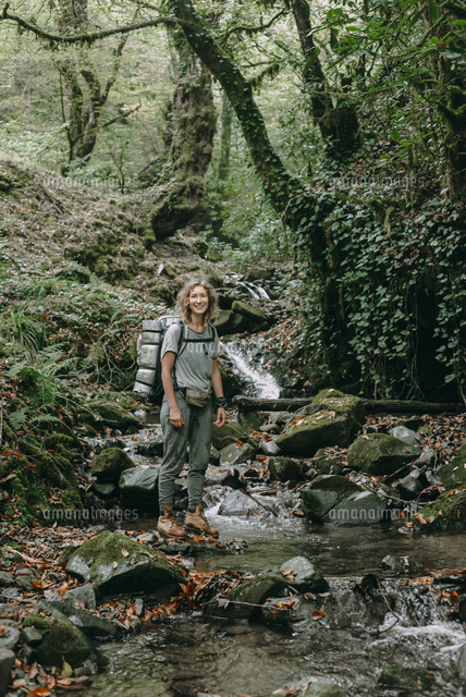 Caucasian woman backpacking across forest stream