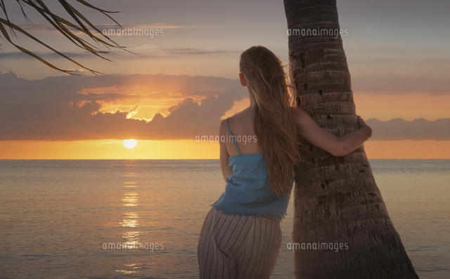 Caucasian woman leaning on palm tree near ocean