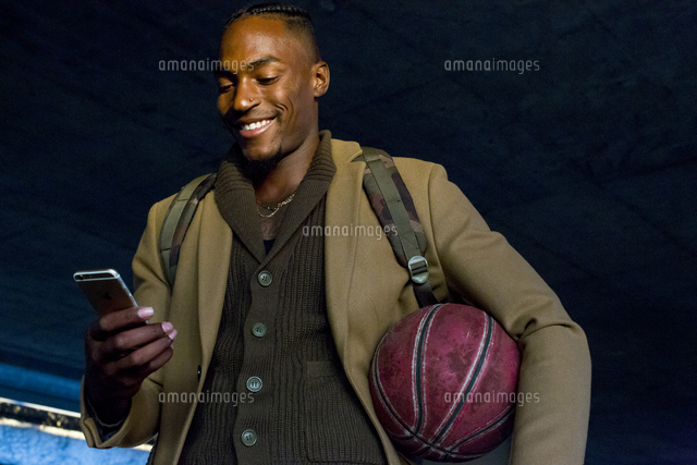 Black man holding basketball texting on cell phone
