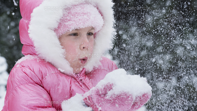 Caucasian girl wearing pink coat blowing snow