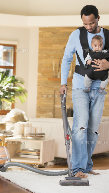 Black father with son in baby carrier vacuuming rug