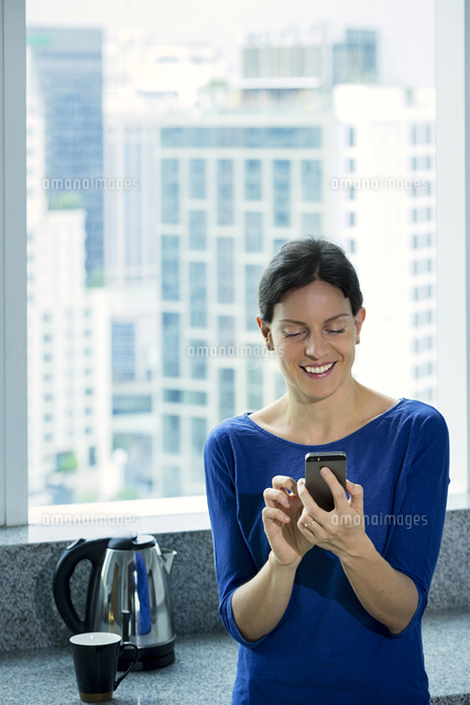 Caucasian woman texting on cell phone near window
