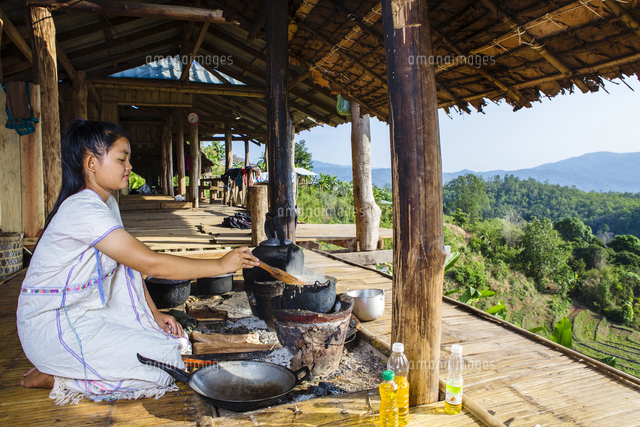 Asian woman cooking on patio outdoors