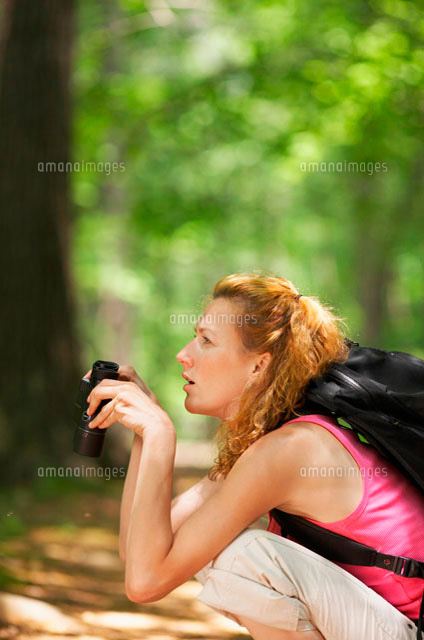Woman crouching and using binoculars