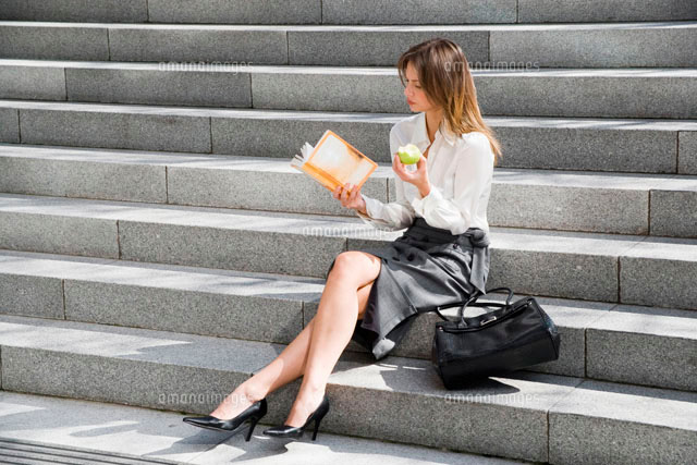Young woman reading and eating on steps