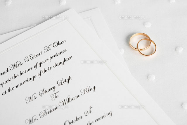 Wedding rings beside invitations