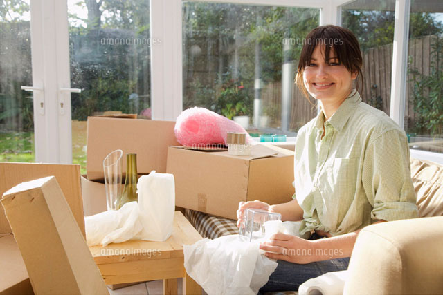 Woman Packing Boxes in Sunroom