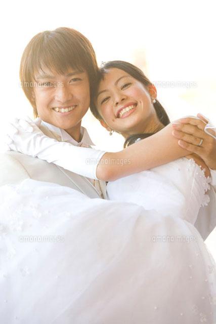 新婦をお姫様抱っこする新郎[11031039194]の写真素材・イラスト