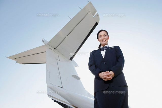 Stewardess in uniform  standing below wing of private jet