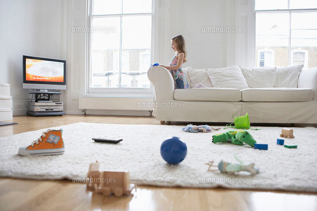 Girl (5-6) watching television  toys on floor in foregroun