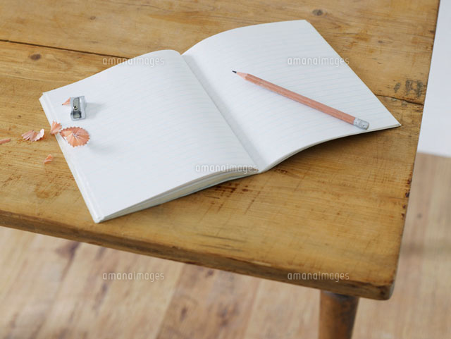 Open notebook with pencil and pencil sharpener on table  e
