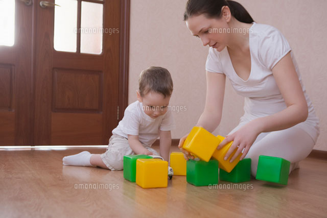 Mother and son play with green and yellow building blocks