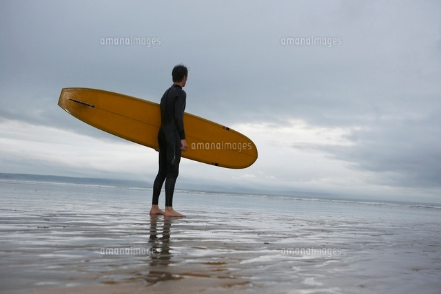 Surfer carrying surfboard on beach side view low angle view