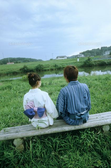 草原のベンチに座る浴衣のカップル後姿 の写真素材 イラスト素材 アマナイメージズ