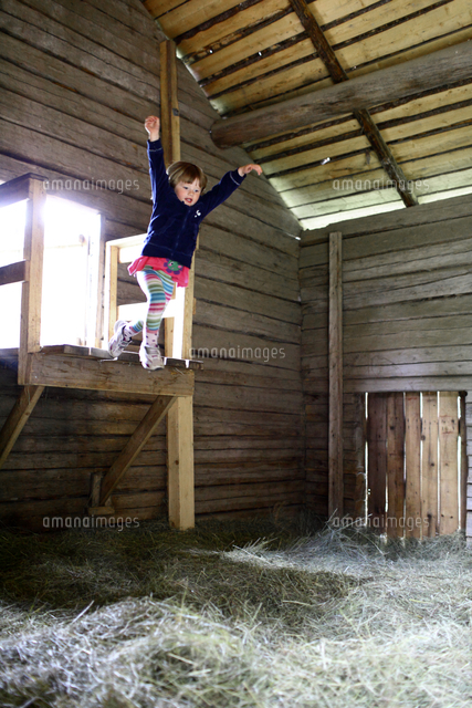 Girl jumping on hay in barn