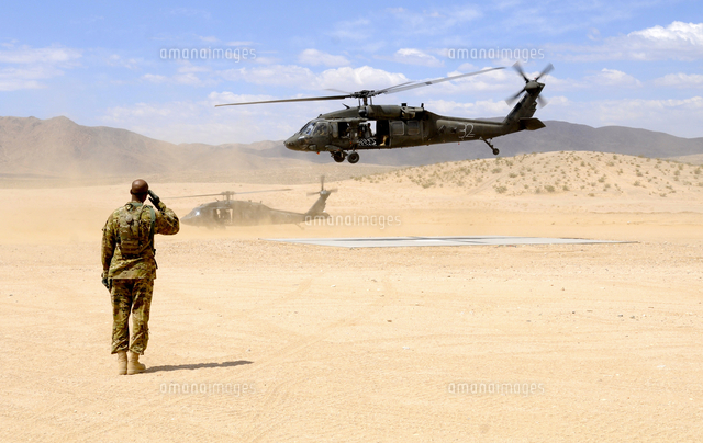 Brigade aviation officer salutes as a UH-60 Black Hawk helic