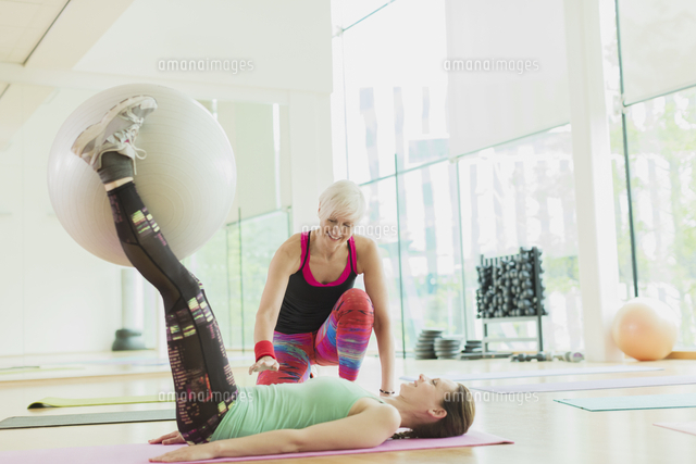 Personal trainer guiding woman with fitness ball between legs