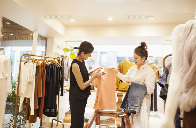Woman working in a fashion boutique in Tokyo, Japan, serving a customer.