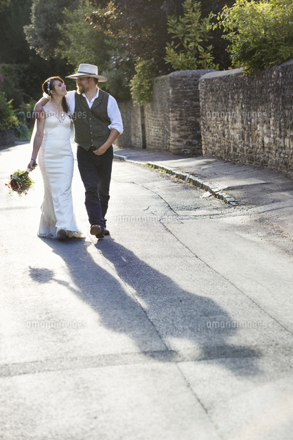 Bride and groom walking along a rural street.