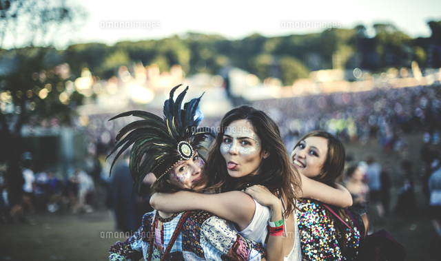 Three young women at a summer music festival feather headdress and faces painted, smiling at camera,