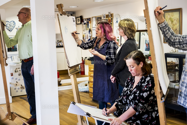 Group of artists standing and sitting at easels, drawing.