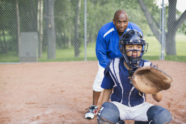 Coach standing behind young male baseball catcher.
