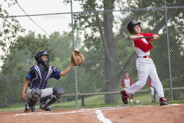 Young male baseball player swinging at baseball.