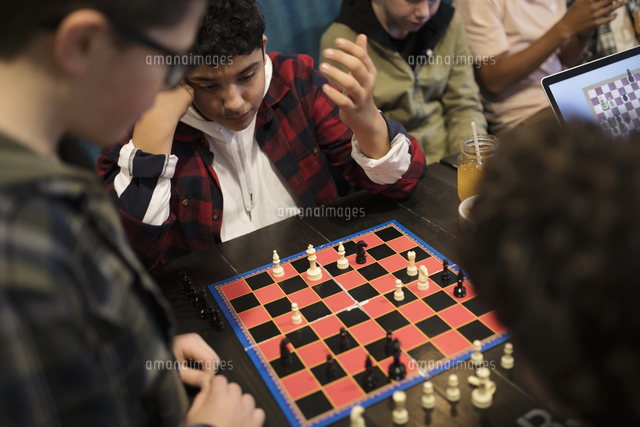 Tween boy friends playing chess at cafe table