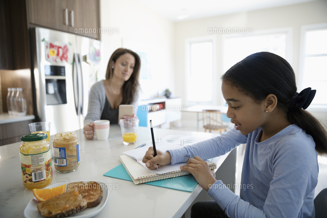 Mother using smart phone while daughter does homework in morning kitchen