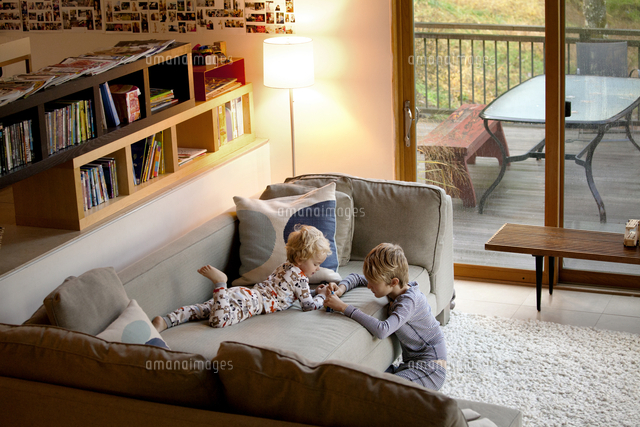 Brothers ( 2-3, 8-9 ) playing on couch in morning