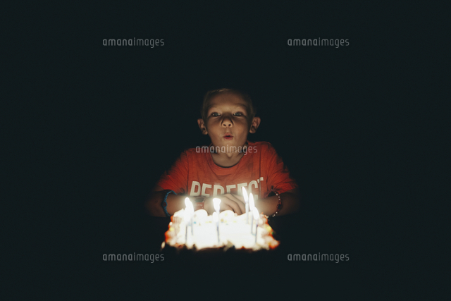 Cute boy blowing birthday candles in darkroom