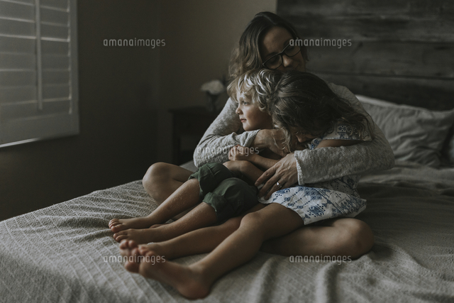 Woman embracing children while sitting on bed