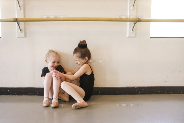 Playful girl tickling friend while sitting in ballet studio