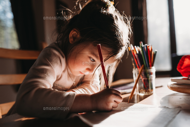 Girl drawing with colored pencil on paper while sitting at table
