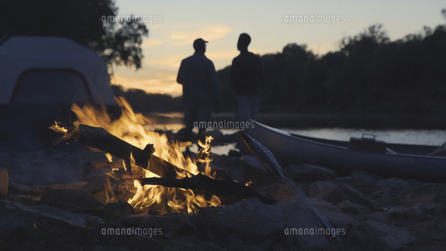 Silhouette father and son standing at lakeshore with campfire burning in foreground