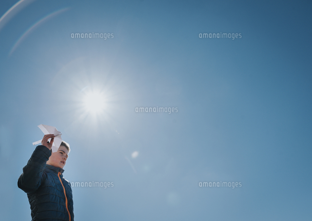 Low angle view of boy holding paper airplane while standing against clear blue sky during sunny day