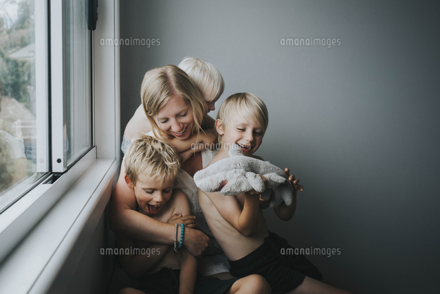 Happy mother with children sitting by window at home