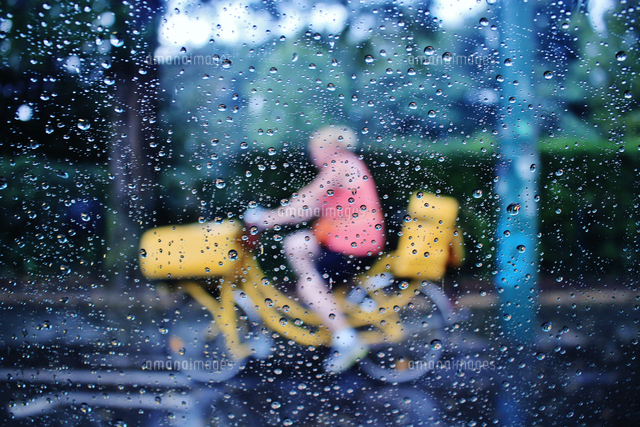 作品番号:11115003324  作品タイトル:Child Riding Bicycle Seen Through Wet Glass Window During Monsoon