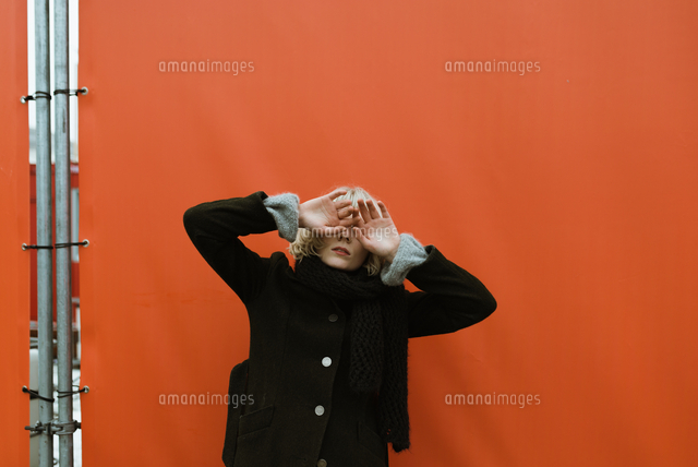 作品番号:11115022110  作品タイトル:Young Woman Covering Eyes While Standing Against Orange Canvas