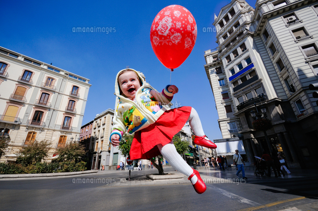 作品番号:11115022500  作品タイトル:Girl With Balloon In Mid-air Against Building Against Blue Sky