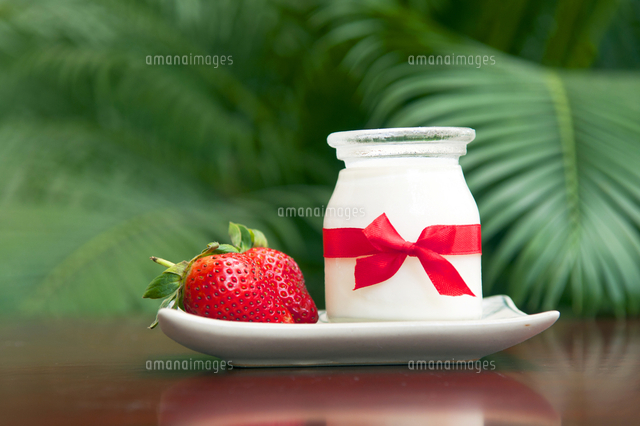 Jar With Yogurt And Strawberries In Plate On Table
