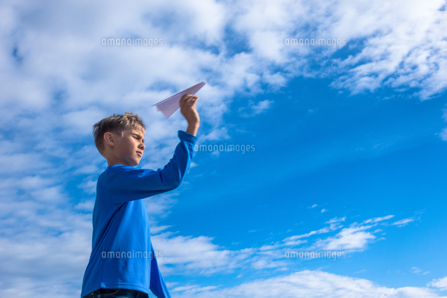 Boy Holding Paper Airplane While Standing Against Sky
