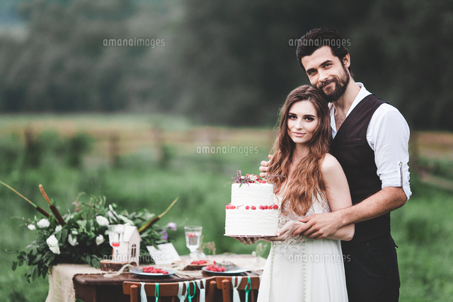 Portrait Of Smiling Couple Holding Wedding Cake At Farm